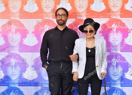 Yoko Ono and Sean Lennon stand beside the stamp design