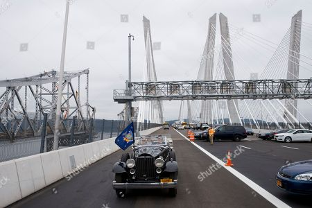New York Gov. Andrew Cuomo drives a 1932 Packard as he officially opens the Gov. Mario M. Cuomo Bridge, in Nyack, N.Y. A portion of the old Tappan Zee Bridge is at left