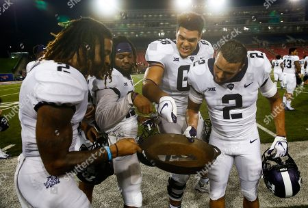"""TCU teammates Jaelan Austin, left, Tony James, second from left, Anthony McKinney, second from right, and Niko Small, right, celebrate with the """"Iron Skillet"""" trophy following their teams win over SMU during an NCAA college football game, in Dallas. TCU won 42-12"""