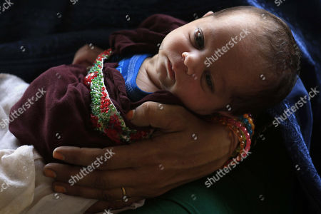 An Afghan Refugee Woman Holds Her Baby Child As She Waits To Leave For  Afghanistan, ...