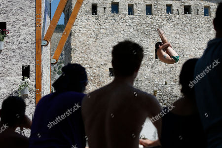 Bosnia Red Bull Cliff Diving World Series 2018. Spectators watch as a diver Steven Lobue, of USA, jumps from the Old Mostar Bridge during the Red Bull Cliff Diving World Series competition in Mostar, 140 kms south of Bosnian capital of Sarajevo, . Twenty four people are competing from the 28 meter high bridge over the river of Neretva. Gary Hunt from UK took first place in male category and Adriana Jimenez from Mexico took first place in female category