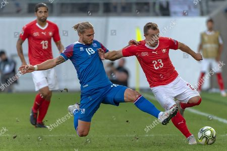 Iceland's Rurik Gislason (L) fights for the ball against Switzerland's Xherdan Shaqiri during the UEFA Nations League group 2 match between Switzerland and Iceland at the Kybunpark stadium in St. Gallen, Switzerland, 08 September 2018.