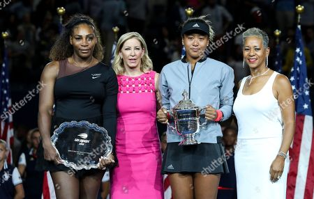 Naomi Osaka celebrates her victory in the women's final with Serena Williams, Chris Evert and Katrina Adams (r)