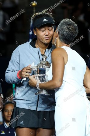Naomi Osaka celebrates her victory in the women's final and is presented the trophy by Katrina Adams