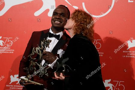Director Jennifer Kent, right, kisses actor Baykali Ganambarr as they hold the Special Jury Prize award and the Best Young Actor award for 'The Nightingale' at the awards photo call of the 75th edition of the Venice Film Festival in Venice, Italy
