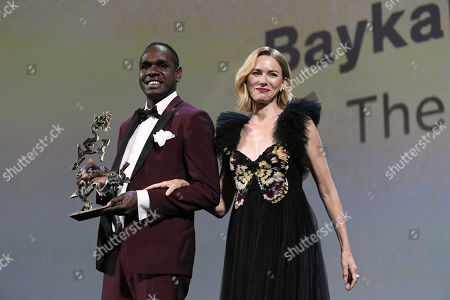Baykali Ganambarr receives the ' Marcello Mastroianni ' Award for Best New Young Actor or Actress for 'The Nightingale' from jury member Naomi Watts