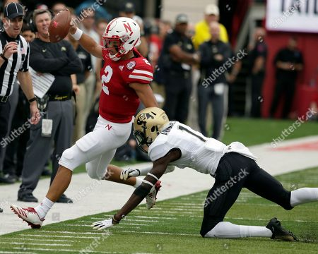 Nebraska quarterback Adrian Martinez (2) runs out of bounds against Colorado defensive back Delrick Abrams Jr. (1) during the first half of an NCAA college football game in Lincoln, Neb