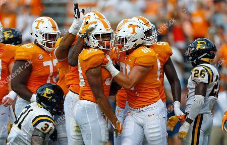 Tennessee running back Jeremy Banks (33) is congratulated by tight end Austin Pope (81) and others after scoring a touchdown in the first half of an NCAA college football game against East Tennessee State University, in Knoxville, Tenn
