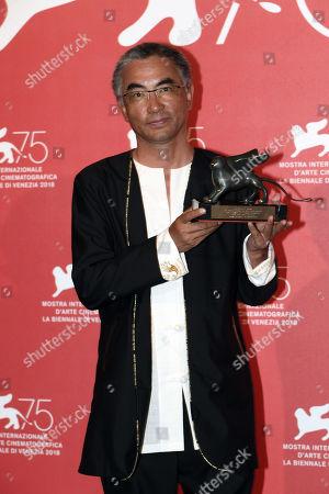 Pema Tseden poses with Orizzonti Award for Best Screenplay Award forJinpa
