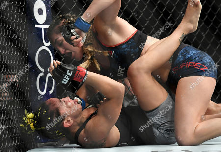 Tatiana Suarez, top, punches Carla Esparza during their strawweight mixed martial arts bout at UFC 228, in Dallas