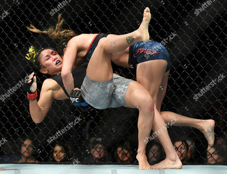 Tatiana Suarez, top, takes down Carla Esparza during their strawweight mixed martial arts bout at UFC 228, in Dallas