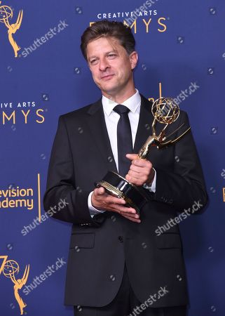 """Cyrille Aufort, winner of the award for outstanding music composition for a limited series, movie or special (original dramatic score) for """"March of the Penguins 2: The Next Step"""" poses in the press room during night one of the Creative Arts Emmy Awards at The Microsoft Theater, in Los Angeles"""