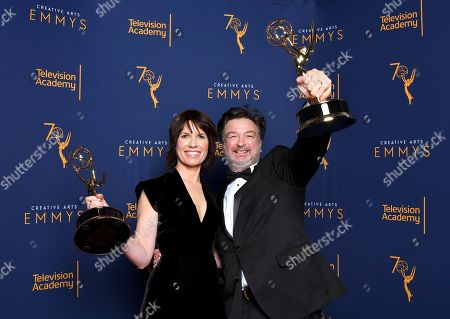"""Stock Picture of Deborah Riley, Paul Ghirardani. Deborah Riley, left, and Paul Ghirardani winners of the award for outstanding production design for a narrative period or fantasy program (one hour or more) """"Game of Thrones, Dragonstone"""" pose for a portrait during night one of the Television Academy's 2018 Creative Arts Emmy Awards at the Microsoft Theater, in Los Angeles"""