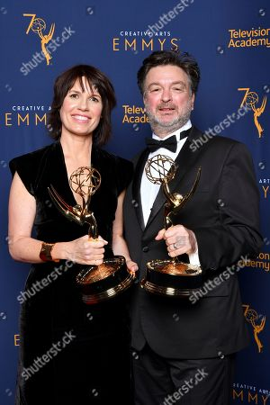 """Stock Photo of Deborah Riley, Paul Ghirardani. Deborah Riley, left, and Paul Ghirardani winners of the award for outstanding production design for a narrative period or fantasy program (one hour or more) """"Game of Thrones, Dragonstone"""" pose for a portrait during night one of the Television Academy's 2018 Creative Arts Emmy Awards at the Microsoft Theater, in Los Angeles"""