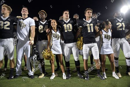 Central Florida quarterback McKenzie Milton (10), long snapper Alex Ward (32), receiver Ke'von Ahmad (84), wide receiver Dontay Mayfield (21) and place kicker Matthew Wright (11) stand with cheerleaders after an NCAA college football game against South Carolina State, in Orlando, Fla. UCF won 38-0