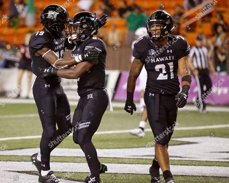 Hawaii wide receiver JoJo Ward (19), left, and running back Fred Holly III (21), right, celebrate with wide receiver Cedric Byrd (6) after a touchdown against Rice during the fourth quarter at an NCAA college football game, in Honolulu