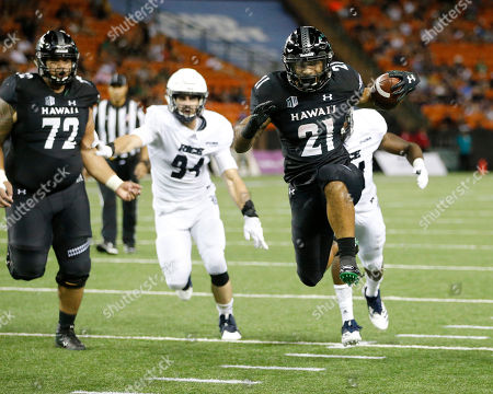 Hawaii running back Fred Holly III (21) leaps over the goal line to make a third-quarter touchdown against Rice at an NCAA college football game, in Honolulu