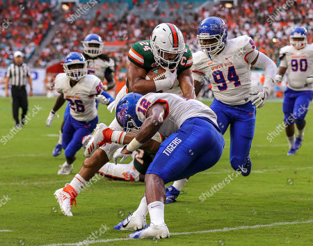 Miami Hurricanes running back Travis Homer (24) advances the ball, tackled by Savannah State Tigers defensive back Isaiah Bennett (12), during the college football game between the Savannah State Tigers and the Miami Hurricanes at the Hard Rock Stadium in Miami Gardens, Florida. The Hurricanes won 77-0