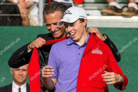 Winner Matthew Fitzpatrick of England (R) receives the red winners jacket from Raynald Aeschlimann (L) CEO Omega after the Omega European Masters Golf Tournament in Crans-Montana, Switzerland, 09 September 2018.