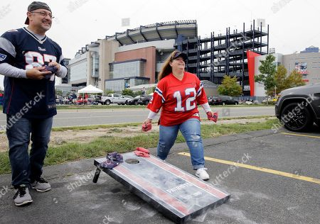 John Brennan, left, of Derry, N.H., and Jeannine Anderson, of Merrimac, Mass., toss the beanbag while tailgating in the parking lot of Gillette Stadium before an NFL football game between the New England Patriots and the Houston Texans, in Foxborough, Mass