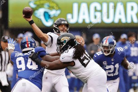 Jacksonville Jaguars quarterback Blake Bortles (5) throws a pass over New York Giants' Dalvin Tomlinson (94) and teammate A.J. Cann (60) during the first half of an NFL football game, in East Rutherford, N.J