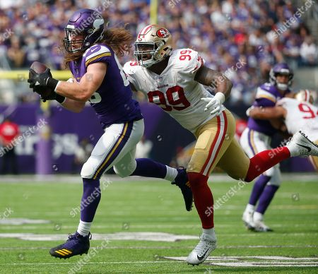 Minnesota Vikings tight end David Morgan, left, catches a pass in front of San Francisco 49ers defensive end DeForest Buckner (99) during the second half of an NFL football game, in Minneapolis. The Vikings won 24-16