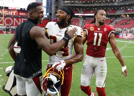 Washington Redskins defensive back Josh Norman (24) hugs Arizona Cardinals defensive back Patrick Peterson as wide receiver Larry Fitzgerald (11) looks on after an NFL football game, in Glendale, Ariz. The Redskins won 24-6