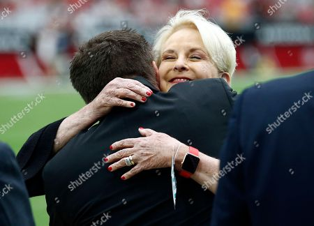Cindy McCain, wife of the late U.S. Sen. John McCain, embraces Arizona Cardinals president Michael Bidwill prior to an NFL football game between the Washington Redskins and the Arizona Cardinals, in Glendale, Ariz