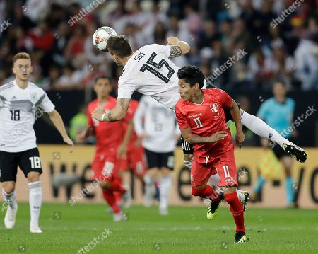 Germany's Niklas Suele, left, and Peru's Raul Mario Ruidiaz fight for the ball during a friendly soccer match between Germany and Peru in Sinsheim, Germany