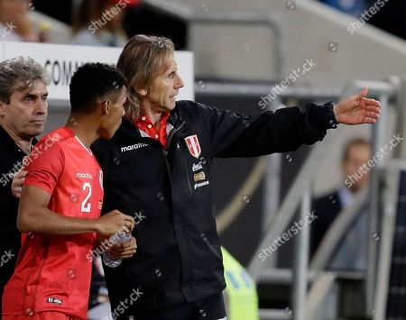 Peru's coach Ricardo Gareca, right, talks to Anderson Santamaria during a friendly soccer match between Germany and Peru in Sinsheim, Germany
