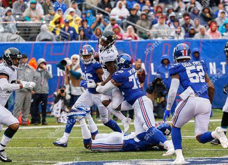 East Rutherford, New Jersey, U.S. - Jacksonville Jaguars running back T.J. Yeldon (24) is tackled by New York Giants defensive end Kerry Wynn (72) during a NFL game between the Jacksonville Jaguars and the New York Giants at MetLife Stadium in East Rutherford, New Jersey. The Jaguars defeated the Giants 20-15