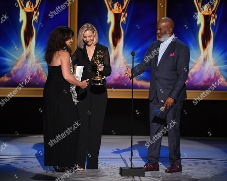 """Lydia Tenaglia, Lisa Kudrow, David Alan Grier. Lisa Kudrow, center, and David Alan Grier present the award for outstanding writing for a nonfiction program to Lydia Tenaglia, left, on behalf of Anthony Bourdain for the """"Southern Italy"""" episode of """"Anthony Bourdain: Parts Unknown"""" during night two of the Television Academy's 2018 Creative Arts Emmy Awards at the Microsoft Theater, in Los Angeles"""