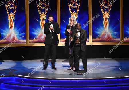 "Joslyn Barnes, Yance Ford. Joslyn Barnes, center, and Yance Ford, right, accept the award for exceptional merit in documentary filmmaking for ""Strong Island"" during night two of the Television Academy's 2018 Creative Arts Emmy Awards at the Microsoft Theater, in Los Angeles"