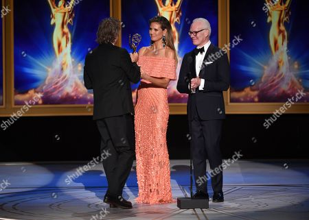 """Stock Picture of Brett Morgen, Heidi Klum, Tim Gunn. Tim Gunn, from right, and Heidi Klum present Brett Morgen with the award for outstanding directing for a documentary/nonfiction program for """"Jane"""" during night two of the Television Academy's 2018 Creative Arts Emmy Awards at the Microsoft Theater, in Los Angeles"""