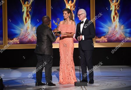 "Yance Ford, Heidi Klum. Yance Ford, left, accepts the award for exceptional merit in documentary filmmaking for ""Strong Island"" from Heidi Klum, center, and Tim Gunn during night two of the Television Academy's 2018 Creative Arts Emmy Awards at the Microsoft Theater, in Los Angeles"