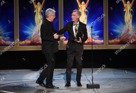 """Stock Photo of Bill Nye, Gregg Field. Bill Nye, right, presents the award for outstanding music direction for """"Tony Bennett: The Library of Congress Gershwin Prize for Popular Song"""" to Gregg Field during night two of the Television Academy's 2018 Creative Arts Emmy Awards at the Microsoft Theater, in Los Angeles"""