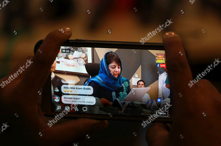 A Kashmiri journalist steaming live with his mobile phone as Peoples Democratic Party (PDP) president and former chief minister of Jammu Kashmir,  Mehbooba Mufti addressing a press conference in Srinagar, the summer capital of Indian Kashmir, 10 September 2018.  Both PDP and National Conference (NC) have announced boycott of the upcoming municipal polls and Panchayat polls, citing unconducive atmosphere  in Kashmir over a legal challenge to Article 35-A of the Indian constitution which defines permanent residents of Jammu and Kashmir and prevents non-locals from buying or owning property in the state. Both PDP and NC demand protection to Article 35-A.