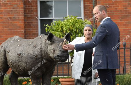 Prince William talks to artist Nancy Fouts at 'The Tusk Rhino Trail' celebration at Kensington Palace.