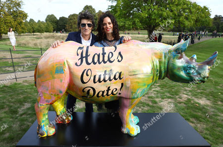 Ronnie Wood and Sally Wood pose with the rhino painted by artist Harland Miller