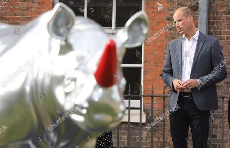 Prince William views a 'rhino' painted by artist Gerry McGovern at 'The Tusk Rhino Trail' celebration at Kensington Palace.