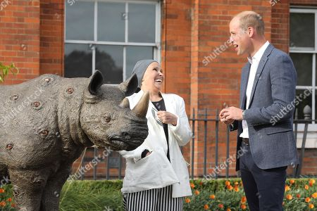 Stock Image of Prince William talks to artist Nancy Fouts at 'The Tusk Rhino Trail' celebration at Kensington Palace.