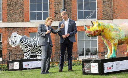 Prince William talks to artist Harland Miller at 'The Tusk Rhino Trail' celebration at Kensington Palace.