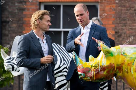 Britain's Prince William, Duke of Cambridge (R) talks to artist Harland Miller (L) at Kensington Palace to celebrate the Tusk Rhino Trial, in London, Britain, 10 September 2018. The Tusk Rhino Trail offers art installation around London, to draw attention to the endangered species.