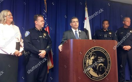 Stock Photo of California Attorney General, Xavier Becerra, at podium, and other officials announce indictments of 32 members of purported street gangs on charges of stealing more than $1 million using an unusually sophisticated credit card fraud, at a news conference in Sacramento, Calif., . From left are Deputy Attorney General Tawnya Austin, who heads the attorney general's e-crimes unit; Walnut Creek Police Chief Tom Chaplin; Becerra; Sacramento Police Chief Daniel Hahn; and Vacaville Police Chief John Carli. Authorities said Monday that the BullyBoys and the CoCo Boys street gangs defrauded hundreds of victims across Northern California by breaking into dozens of medical and dental offices to steal credit card terminals and patient records