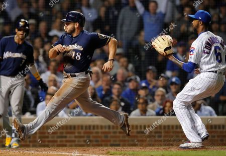 Milwaukee Brewers' Mike Moustakas comes in to score on a wild pitch by Chicago Cubs' Carl Edwards Jr., right, during the sixth inning of a baseball game, in Chicago