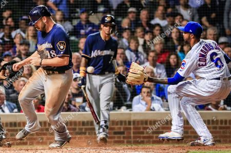 Milwaukee Brewers third baseman Mike Moustakas (L) scores on a wild pitch as Chicago Cubs relief pitcher Carl Edwards Jr. (R) covers home plate in the sixth inning of their MLB game at Wrigley Field in Chicago, Illinois, USA, 10 September 2018.