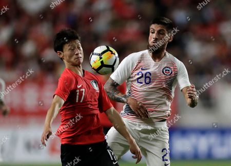 Lee Jae-sung, Ignacio Jeraldino. South Korea's Lee Jae-sung, left, and Chile's Ignacio Jeraldino fight for the ball during a friendly soccer match between South Korea and Chile at Suwon World Cup Stadium in Suwon, South Korea