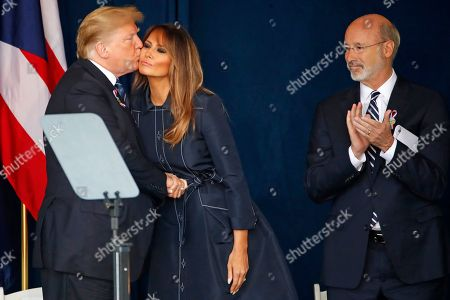 President Donald Trump kisses First Lady Melanie Trump, as Pennsylvania Governor Tom Wolfe looks, after finishing his remarks during the September 11th Flight 93 Memorial Service in Shanksville, Pa