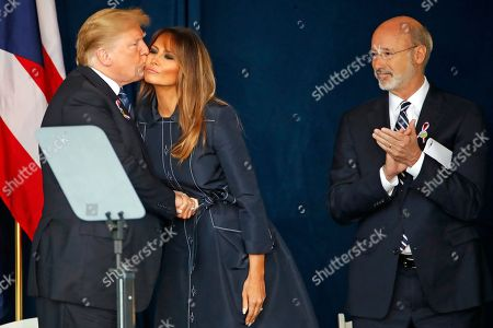 Stock Image of President Donald Trump kisses First Lady Melanie Trump, as Pennsylvania Governor Tom Wolfe looks, after finishing his remarks during the September 11th Flight 93 Memorial Service in Shanksville, Pa