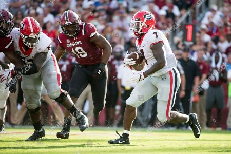 D'Andre Swift, Brad Johnson. Georgia running back D'Andre Swift (7) runs with the ball against South Carolina defensive lineman Brad Johnson (19) during the second half of an NCAA college football game, in Columbia, S.C. Georgia defeated South Carolina 41-17